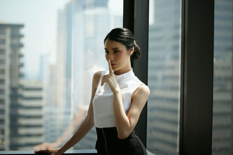 Businesswoman with finger on lips standing against window at office