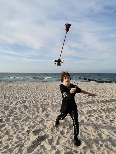 Man with arms raised on beach against sky, juggling