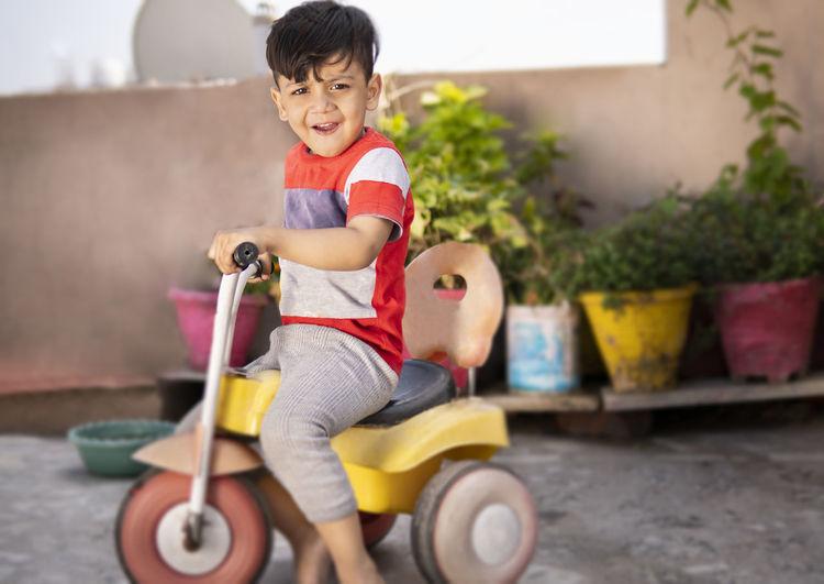 Cute boy riding toy car