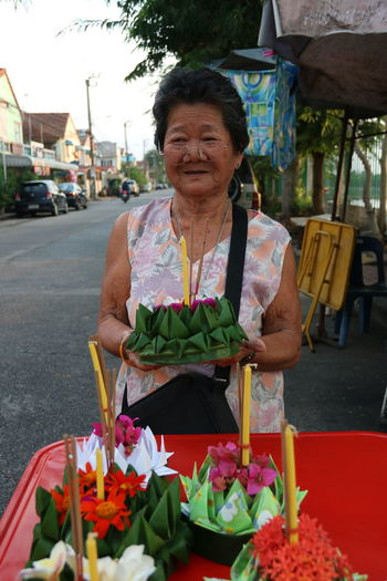 Woman with pink flowers in market