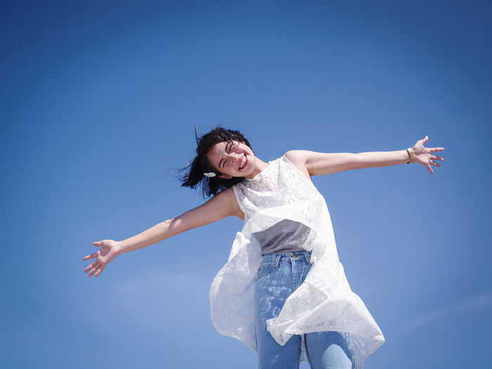 Arms Outstretched Beautiful Woman Blue Cheerful Clear Sky Day Energetic Full Length Fun Happiness Jumping Leisure Activity Lifestyles Long Hair Low Angle View Mid-air Motion Nature One Person Outdoors Real People Sky Smiling Young Adult Young Women