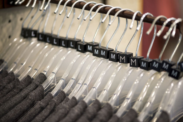 Fashion Hanging S M L Shopping Sizes Tshirt Choice Clothing Fashion Focus On Foreground Hangers In A Row Indoors  Medium Group Of People No People Order Rack Repetition Retail  S M L Xl Selective Focus Silver Colored Store