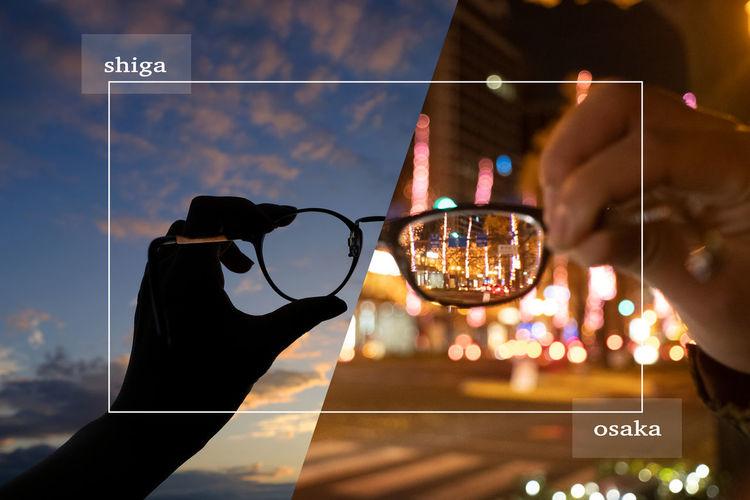 Digital composite image of hand holding sunglasses against sky