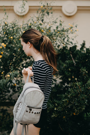 Side view of young woman standing with bag