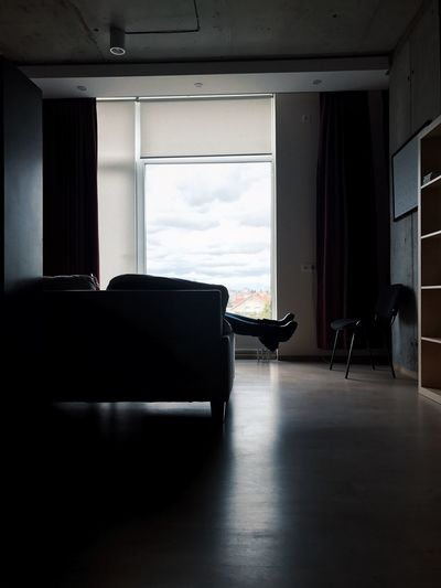 Person relaxing on sofa by window at home