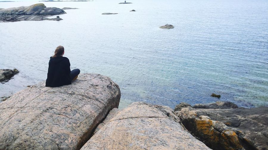 Rear view of woman sitting on rock looking at sea