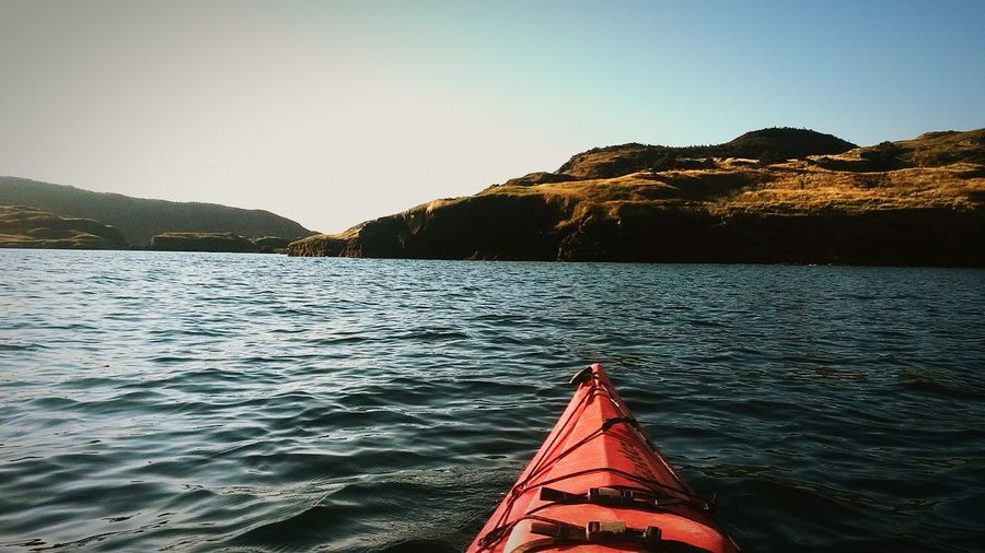 Cropped image of kayak over lake against clear sky