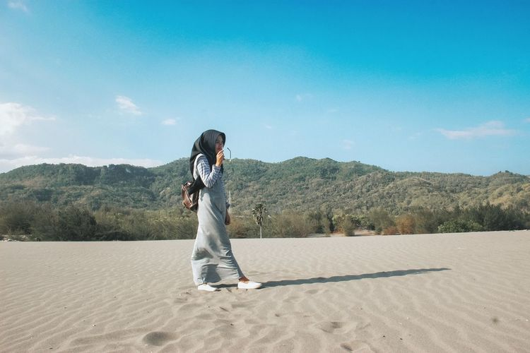 Side view of woman standing on sand against sky