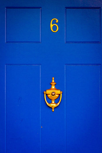 Close-up of yellow sign on blue door