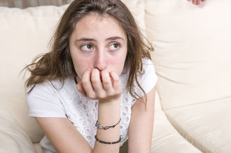 Teen girl is angry on sofa at home. Adolescence  Anger Angry Conflict Couch Frustration FURIOS Girl Issues Problems Sadness Sofa Teen Teenager Upset Worried Worry Young Women