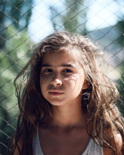 Close-up portrait of girl against chainlink fence
