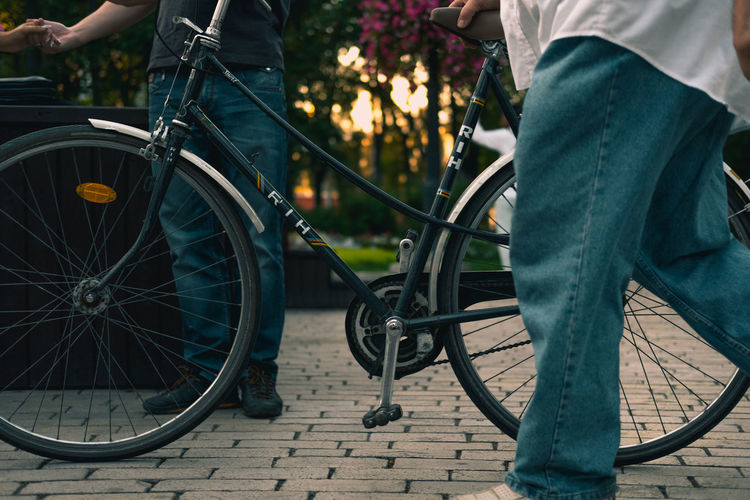Adult Bicycle City Day Human Hand Human Leg Land Vehicle Low Section Men Mode Of Transport Outdoors People Real People Standing Stationary Transportation Two People Urban Transportation Wheel Pants