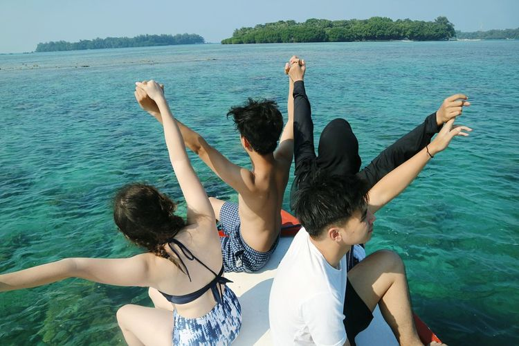 Friends Holding Hands While Sitting On Boat In Sea