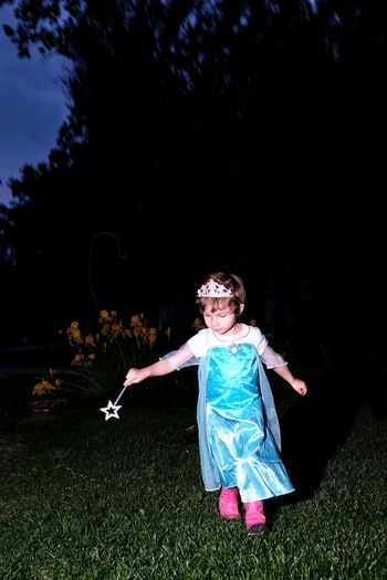 Girl In Fairy Costume Holding Magic Wand On Field At Night