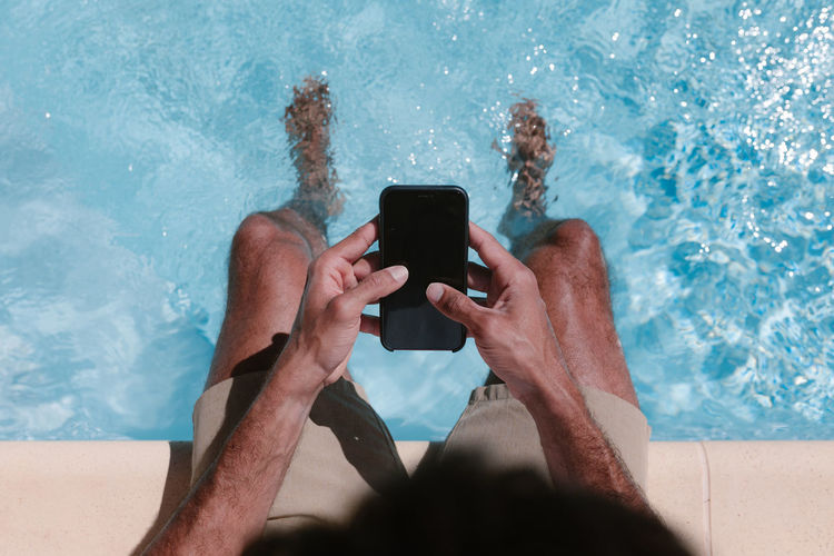 Midsection of man using mobile phone in swimming pool