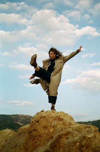 Full length of woman jumping on rock against sky
