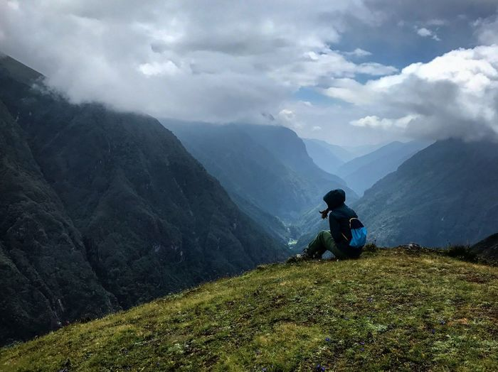 Side view of woman sitting on mountain against cloudy sky
