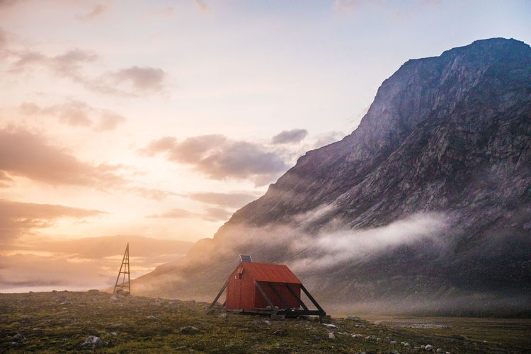 Tent on mountain against sky during sunset