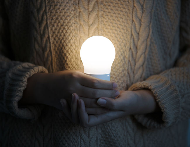 Women hand holding light bulb, concept of save earth Illuminated One Person Lighting Equipment Human Hand Indoors  Hand Human Body Part Close-up Holding Body Part Real People Lifestyles Light Bulb Adult Glowing Technology Midsection Light Electricity  Finger Electric Lamp