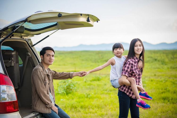 Friends enjoying road trip by car trunk on field