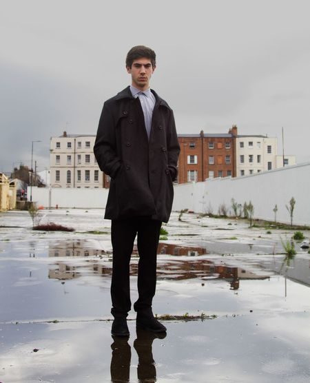Portrait Of Young Man Standing In Puddle