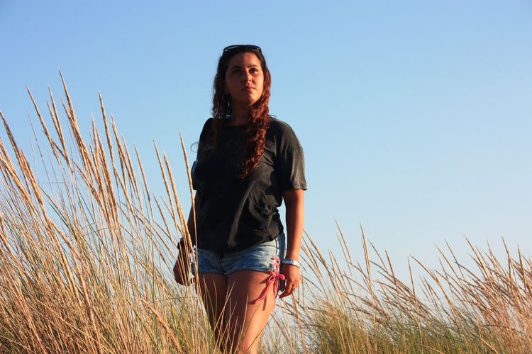 Young tanned woman in shorts at sunset time among the dry vegetation of sea sand dunes in tuscany