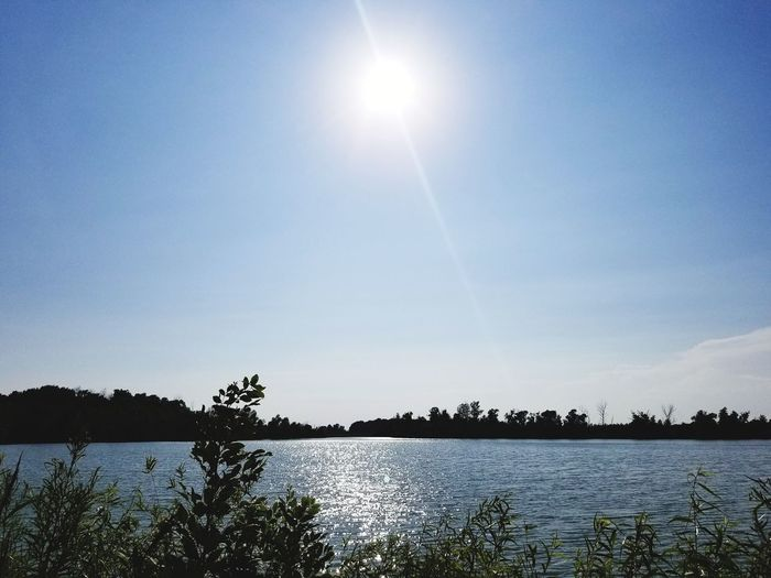 Scenic view of lake against sky on sunny day