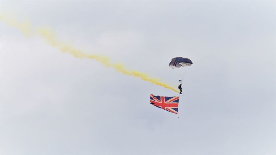 Low angle view of person paragliding with british flag against sky