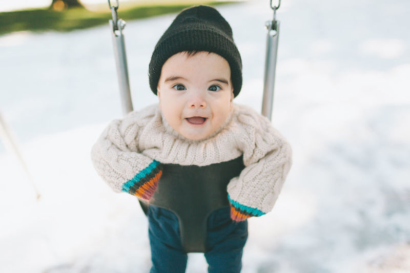 Portrait of cute baby boy swinging during winter
