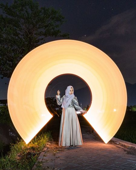 Woman standing with light painting against sky at night