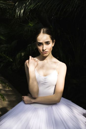 Portrait Of Ballet Dancer Sitting Against Plants