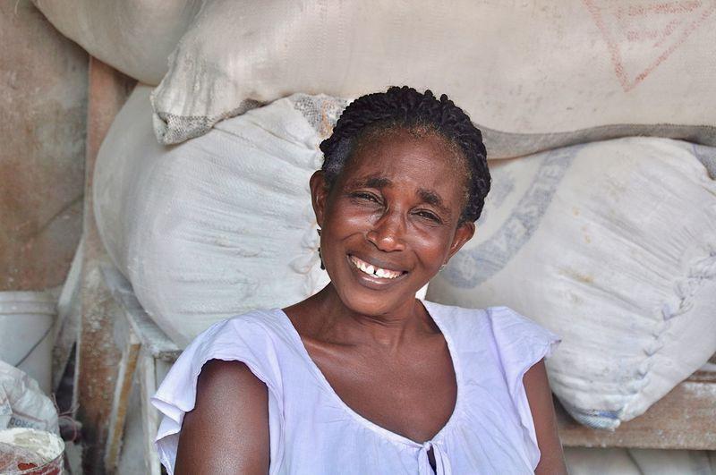 Portrait Of Mature Woman Smiling Against Sacks