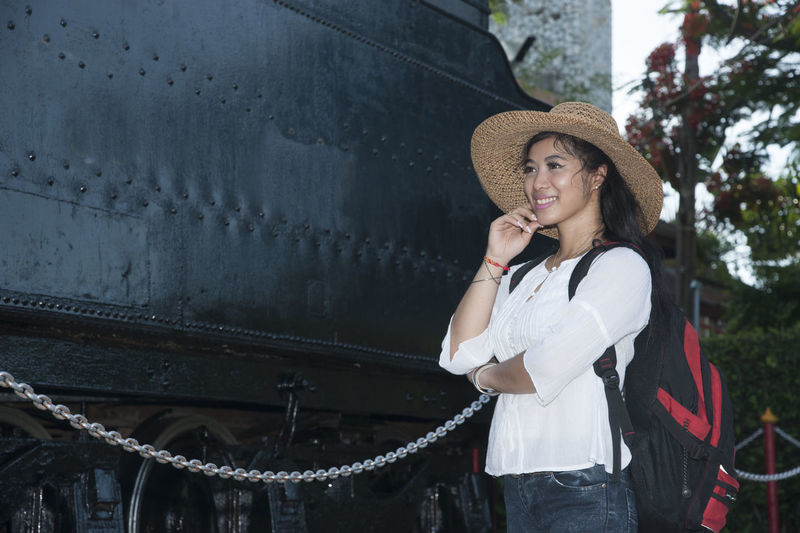 Pretty Asian Women standing and posing at Steam locomotive. Asian  Steam Thailand Adult Bacpacker Beautiful Woman Day Fashion Front View Hat Leisure Activity Lifestyles Locomotive Old One Person Outdoors People Portrait Real People Standing Sun Hat Tourism Travel Destinations Young Adult Young Women