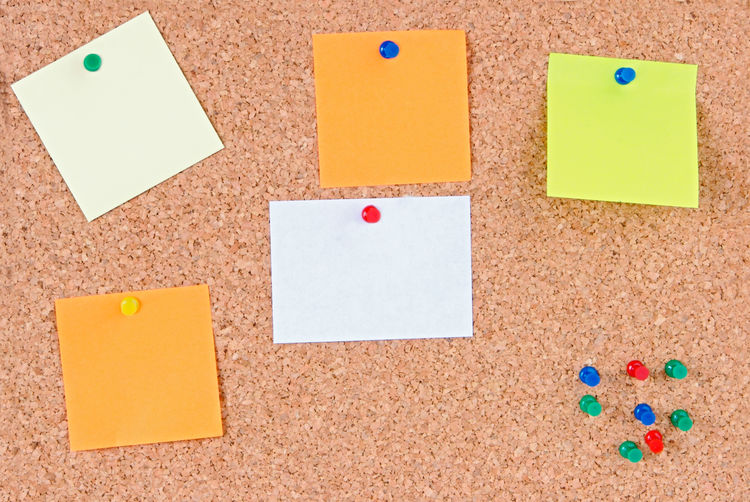 Close-up of colorful blank adhesive notes on bulletin board