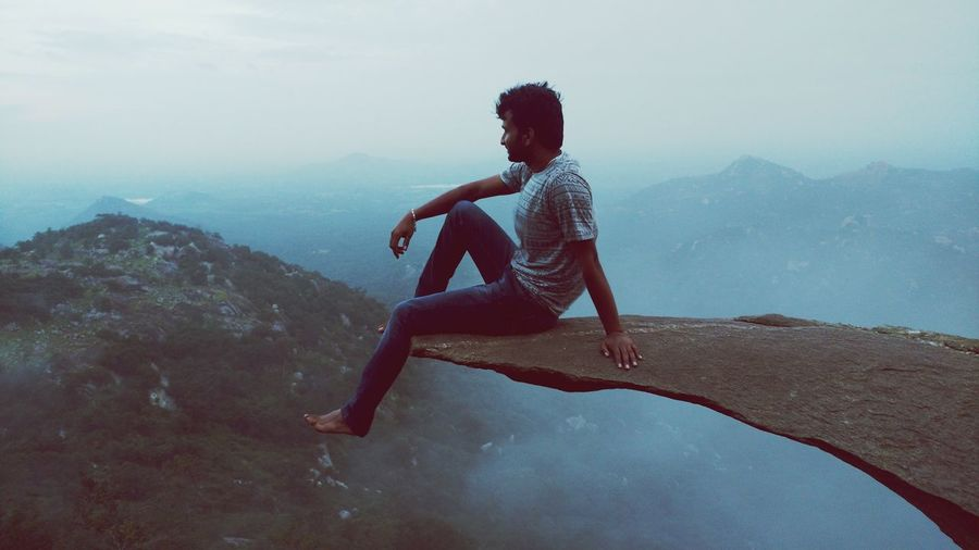 Full length of man sitting on cliff against mountain during foggy weather