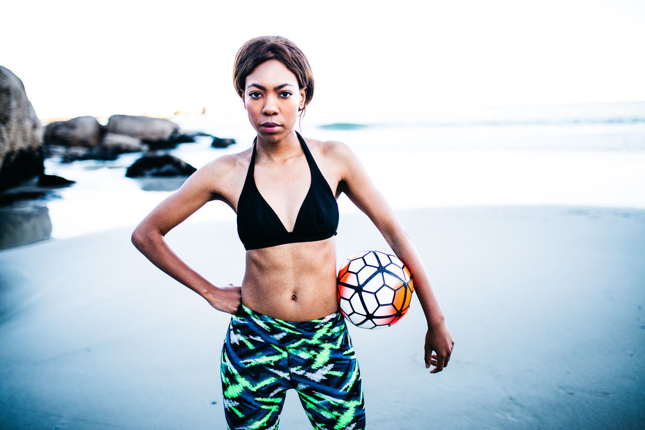 real people, sea, water, one person, beach, standing, young adult, lifestyles, front view, young women, three quarter length, focus on foreground, leisure activity, beautiful woman, outdoors, looking at camera, portrait, vacations, beauty in nature, scenics, nature, day, fashion model, horizon over water, sky, abdomen, people