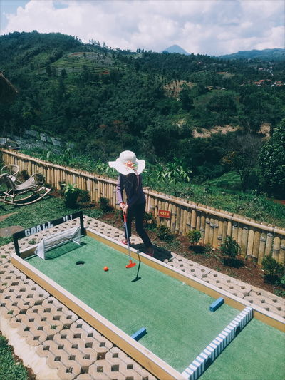 High Angle View Of Girl Playing Miniature Golf