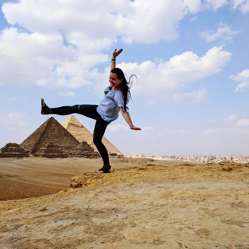 Woman Standing On One Leg Against Pyramids