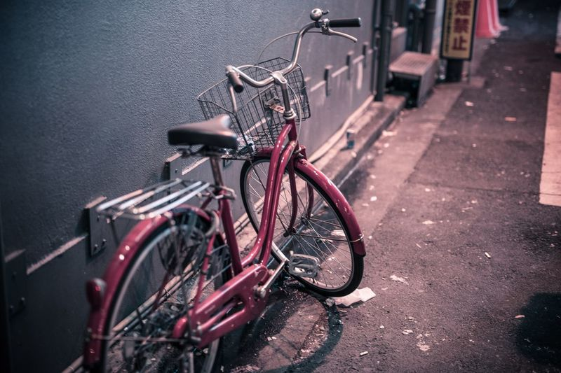 Close-up of bicycle parked on street against wall