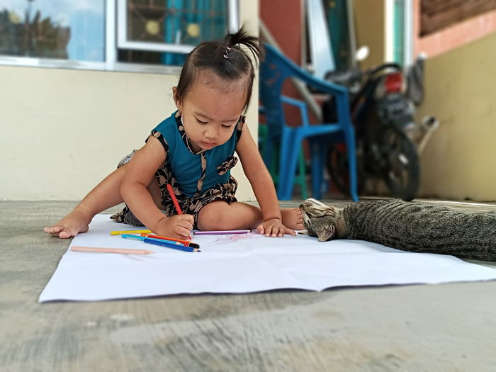 Girl drawing on paper while sitting by cat on floor at home