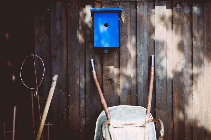 Birdhouse With Wheelbarrow Against Wooden Wall