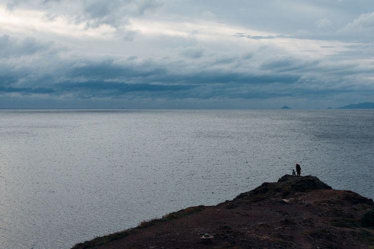 People looking at sea against sky