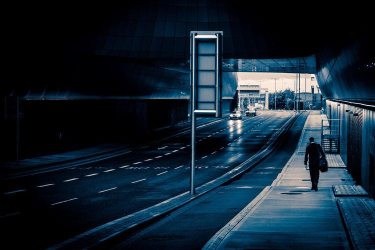 Man Walking On Sidewalk In City