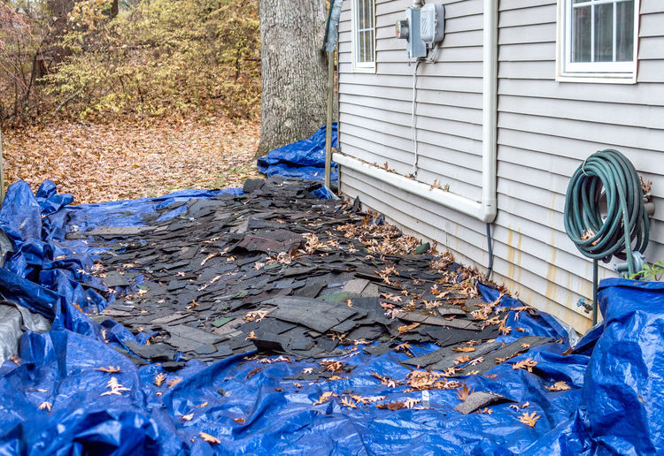 A blue tarp is filled with old shingles removed from the roof of this home