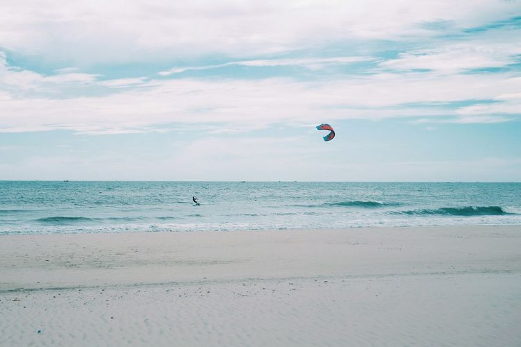 Scenic view of kiteboarder on sea against sky
