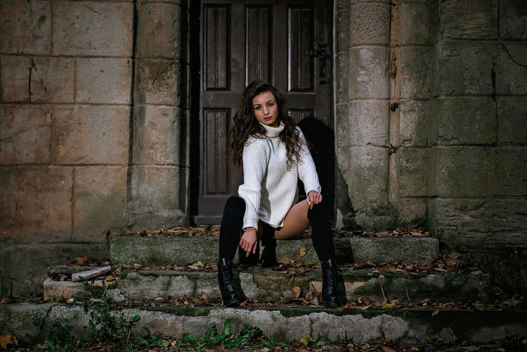 Full length portrait of woman sitting against building
