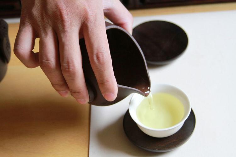 Close-up of hand serving tea