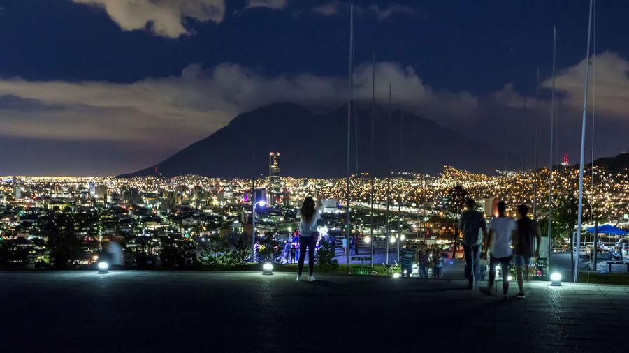 People on walkway against illuminated city at night