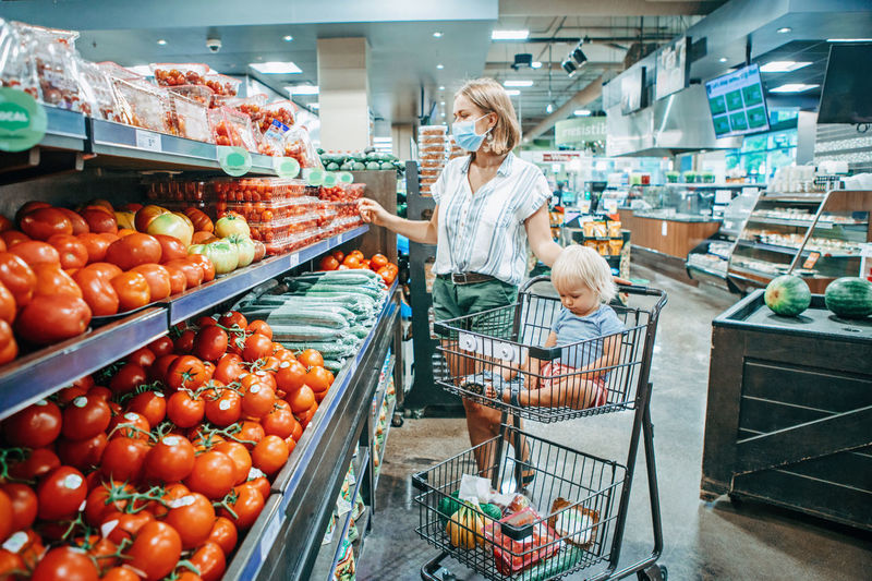 Young mother in protective face mask buying food with kid baby in shopping cart.