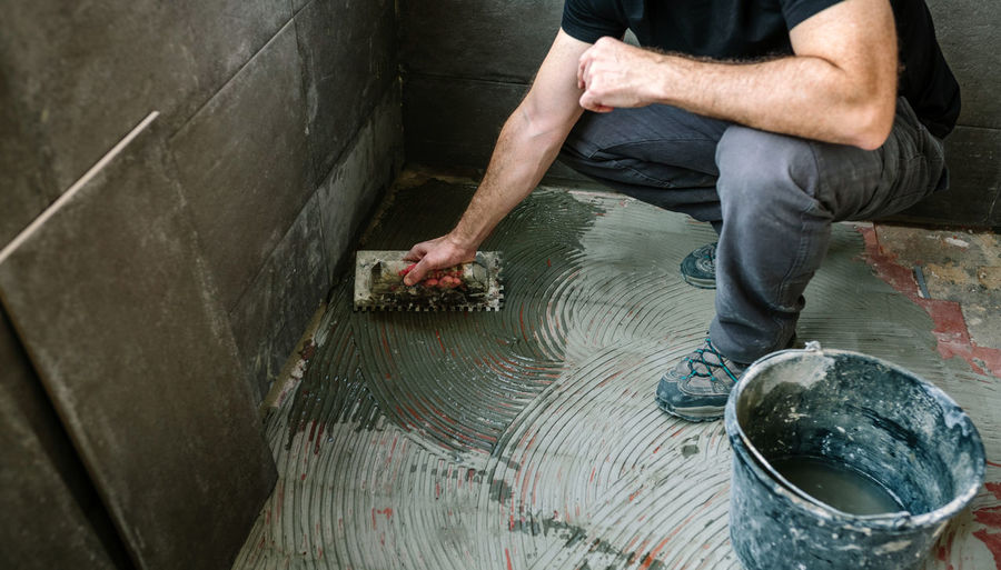Low section of man applying cement on floor